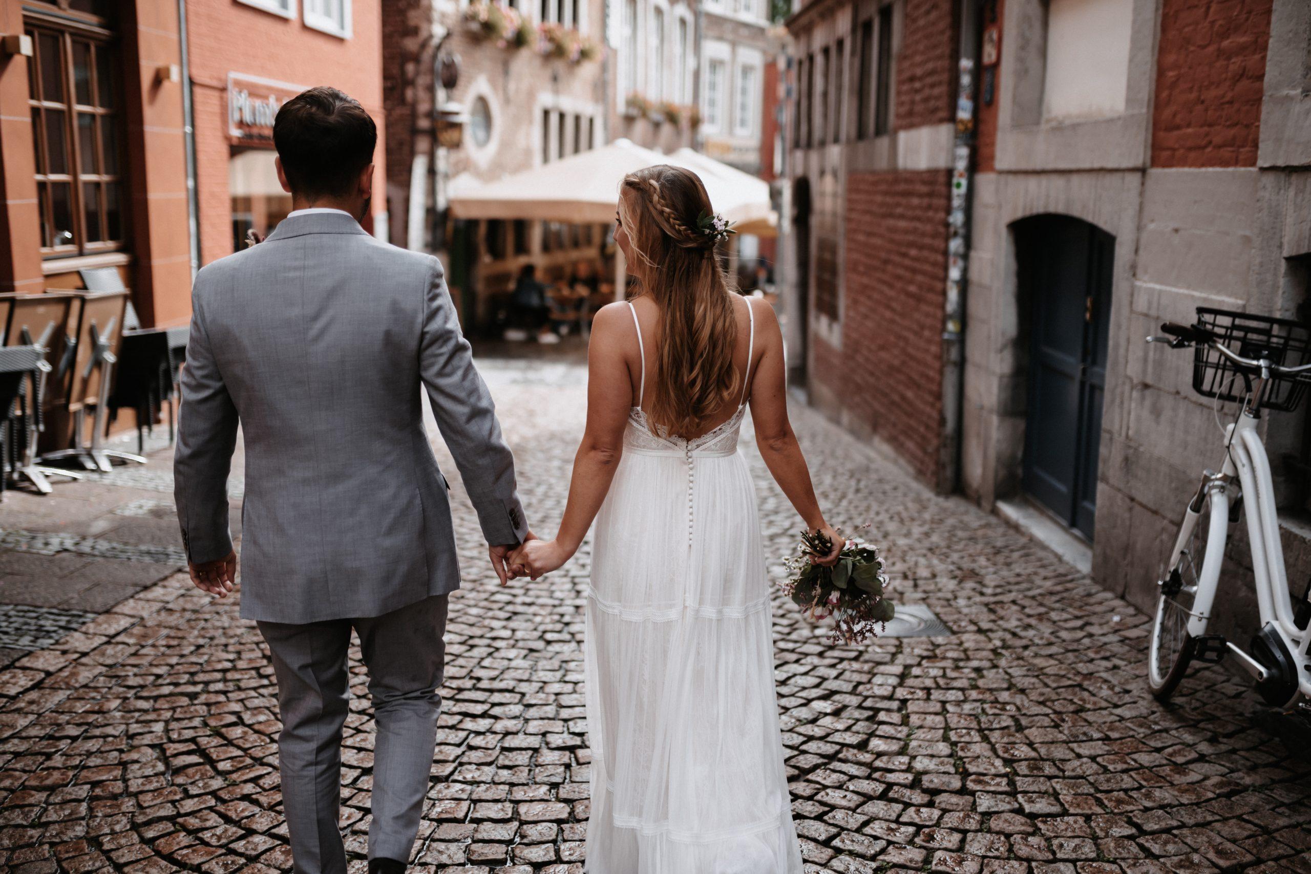 Braut und Bräutigam spazieren durch Aachen