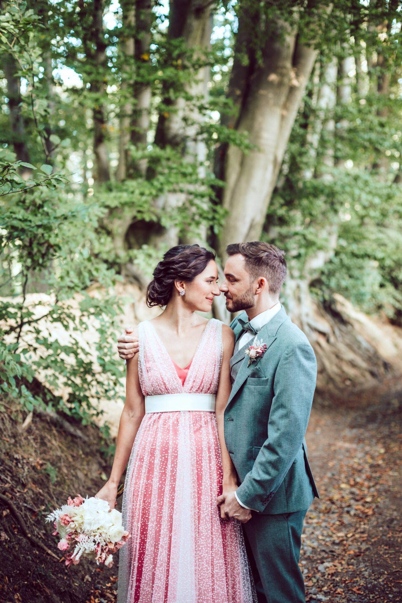 Braut und Bräutigam Arm in Arm schauen sich verliebt an