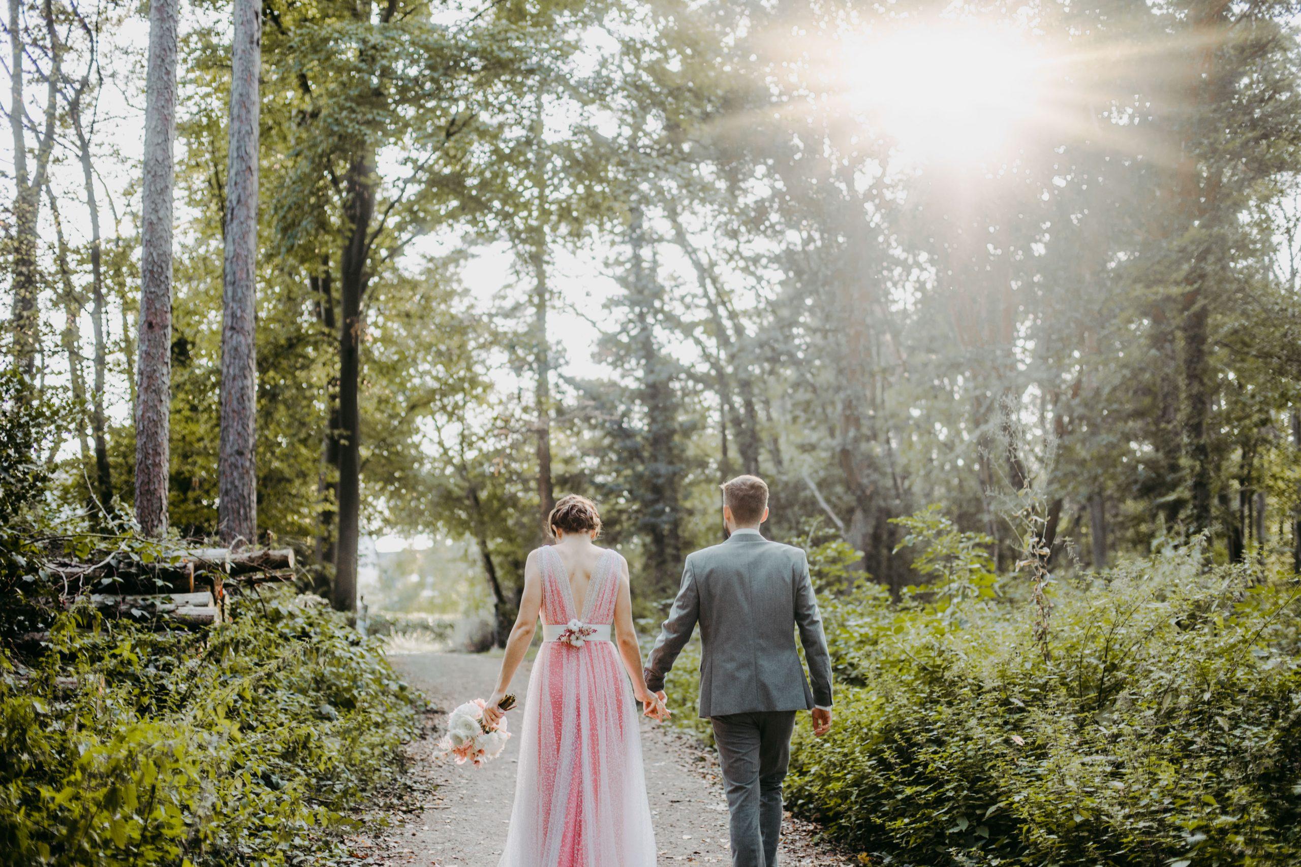 Braut und Bräutigam Hand in Hand im Wald